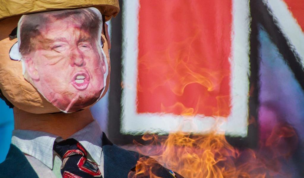 Migrantes queman piñata de Trump para denunciar abusos en Tijuana