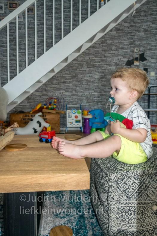 Jayden 20 maanden oud peuter dreumes - poef als stoel en met de voetjes op tafel