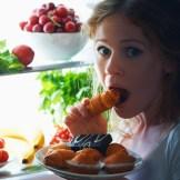 冷蔵庫の中のものを食べる女性