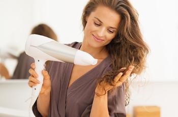 髪の毛をドライヤーで乾かす女性
