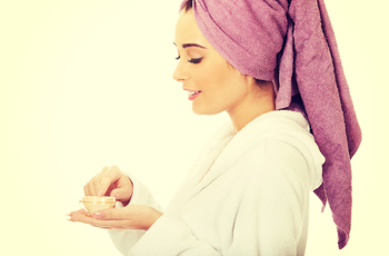 クリームで保湿するバスローブの女性