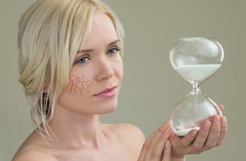 砂時計を持った女性/乾燥した肌