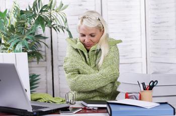 冷えたオフィスで寒がる女性