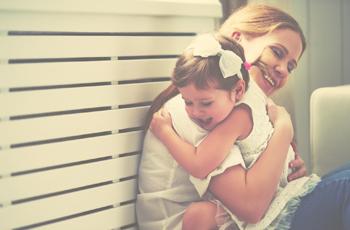 娘を抱きしめる母親