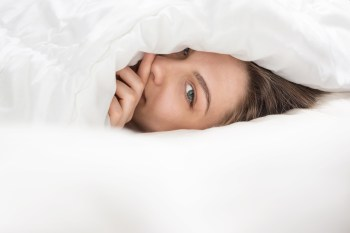 Gorgeous girl peeping from under the white blanket. Sunny pleasant morning. time to wake up. Start a new wonderful day. lovable green eyes looking