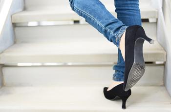 階段をのぼるハイヒールの女性