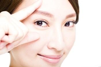 眉毛を指す女性