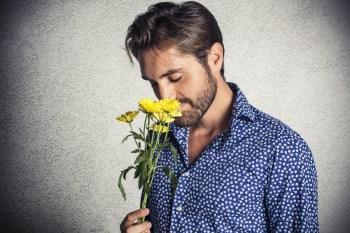 花の香りを嗅ぐ男性