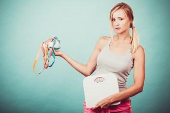 体重計とメジャーを持つ女性