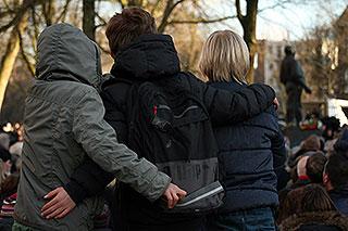 Drie knullen kijkend gearmd naar de kransleggingen bij monument de Dokwerker tijdens de herdenking van de februaristaking