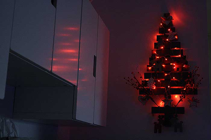 Kleine houten kerstboom met rood sfeerlicht