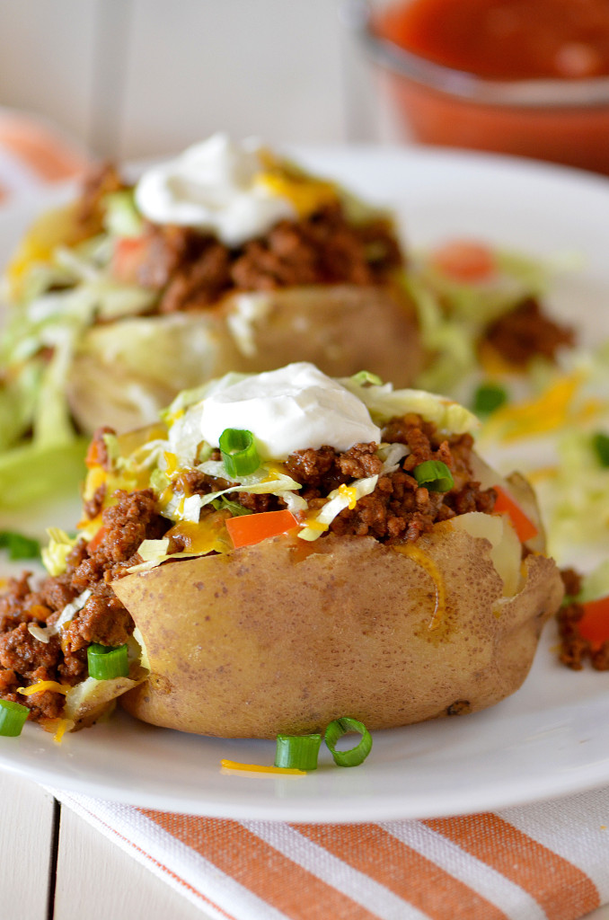"Taco Potatoes Recipe | Life in the Lofthouse ""Taco potatoes take ordinary baked potatoes to new heights! Seasoned ground beef, cheese, lettuce, sour cream and salsa. Everything you love about a taco all over a potato."""