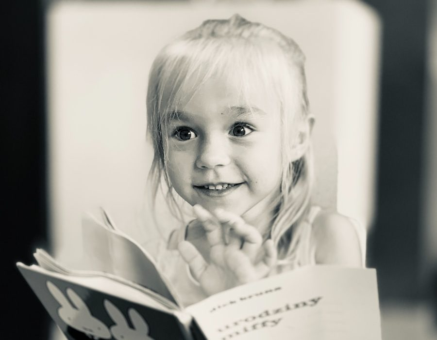 grayscale photo of girl holding book and smiling