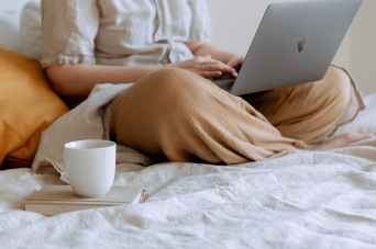 woman lounging with laptop and cup of coffee on the bed