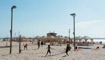 people playing beach volleyball under clear blue sky
