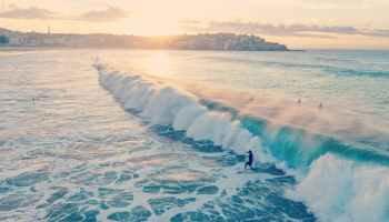 photo of man surfing on ocean waves