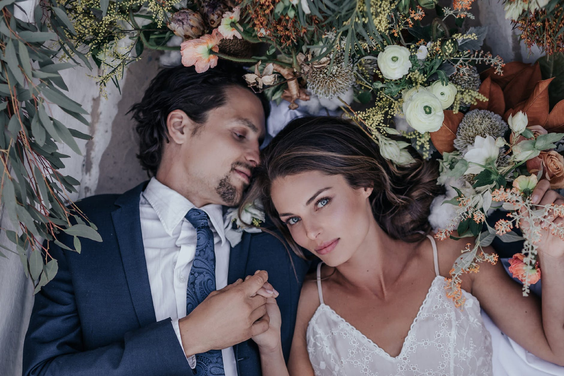 man and woman lying on a bed of flowers