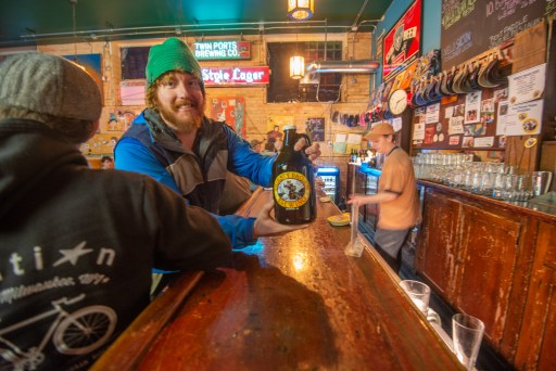 Julien Kegel holds a growler of Thirsty Pagan beer in the bar