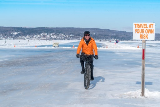 A man rides a bike on the ice road in Bayfield next to a sign that says travel at your own risk.
