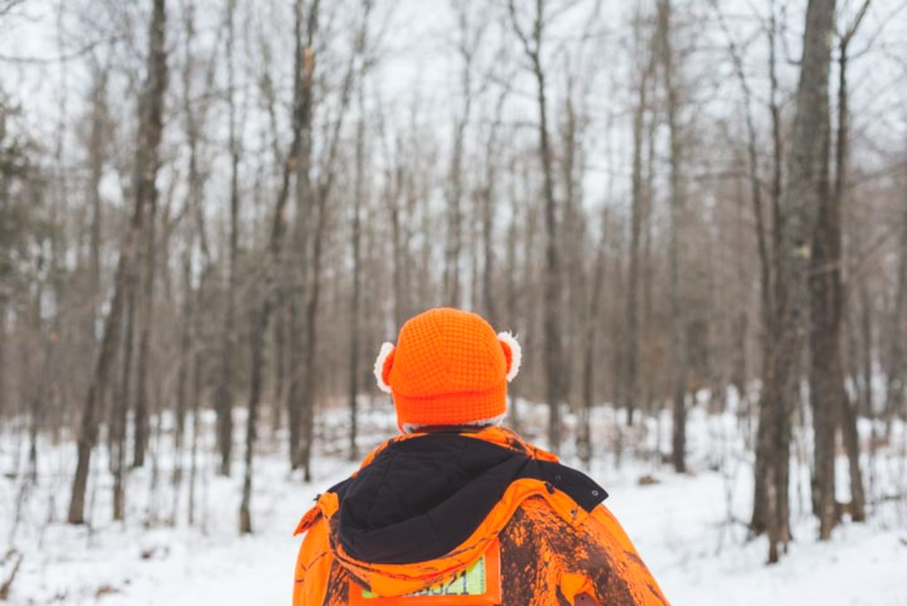 Man in blaze orange in foreground with snow-covered forest in background.