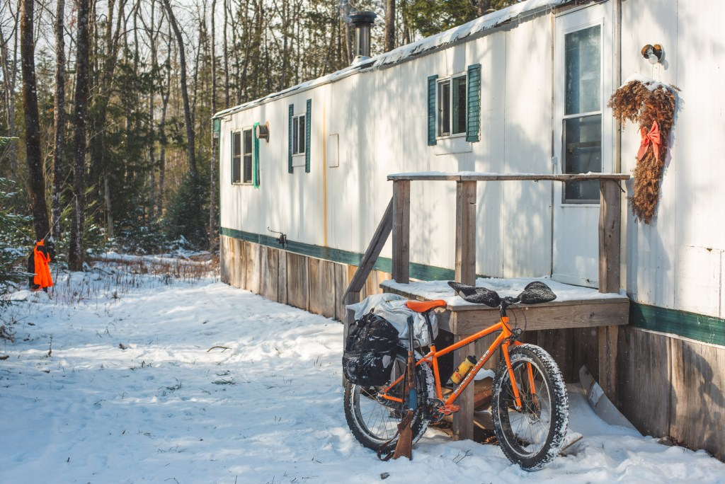 orange fat bike and a rifle lean agains a 70 foot trailer in the woods.