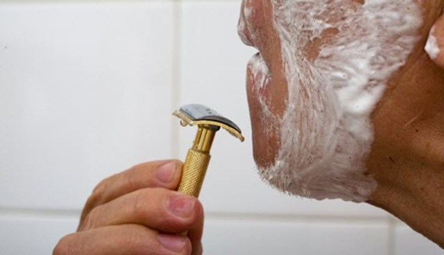 man shaving with a safety razor