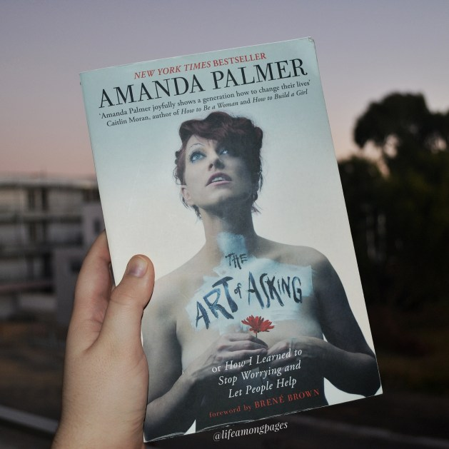 The Art of Asking by Amanda Palmer, held in front of a building under construction and a tree.