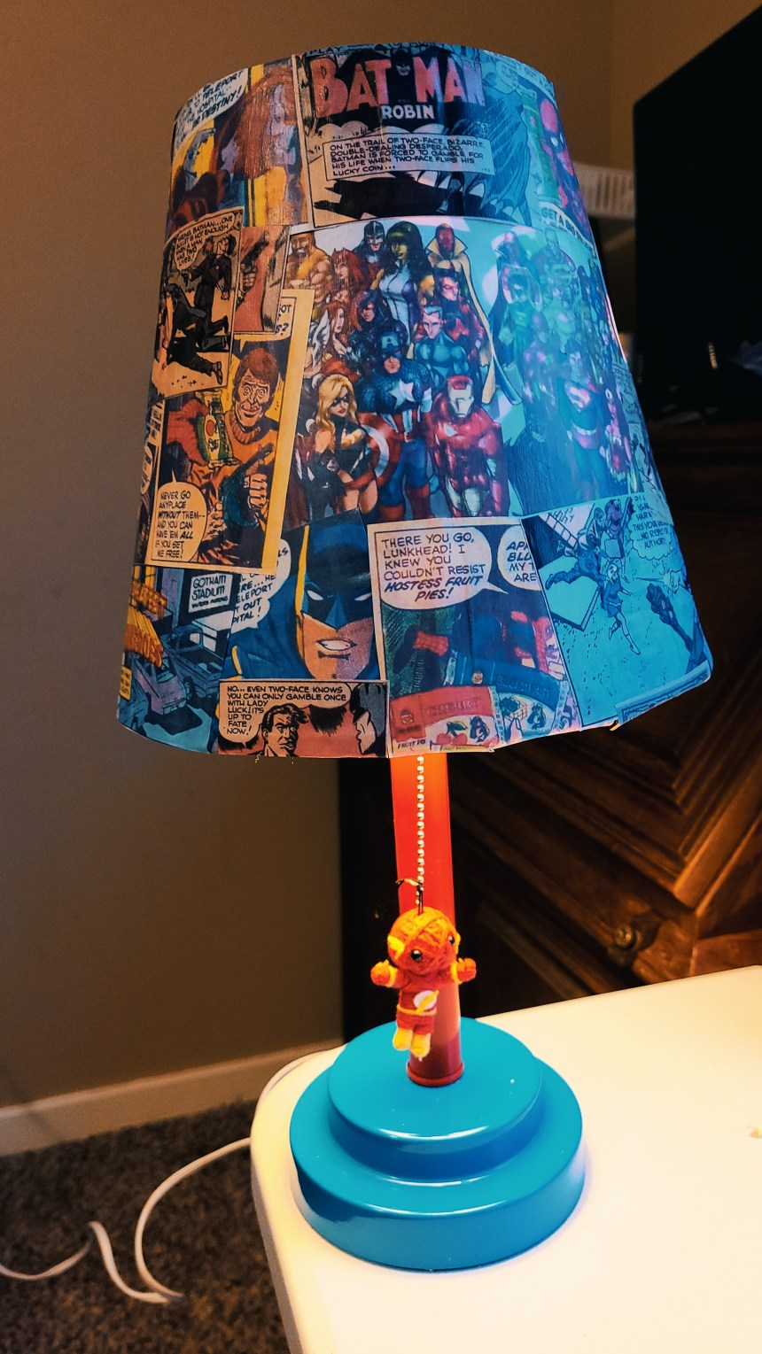Upcycled superhero lamp with string Flash as the on/off pull string, and lamp turned on.