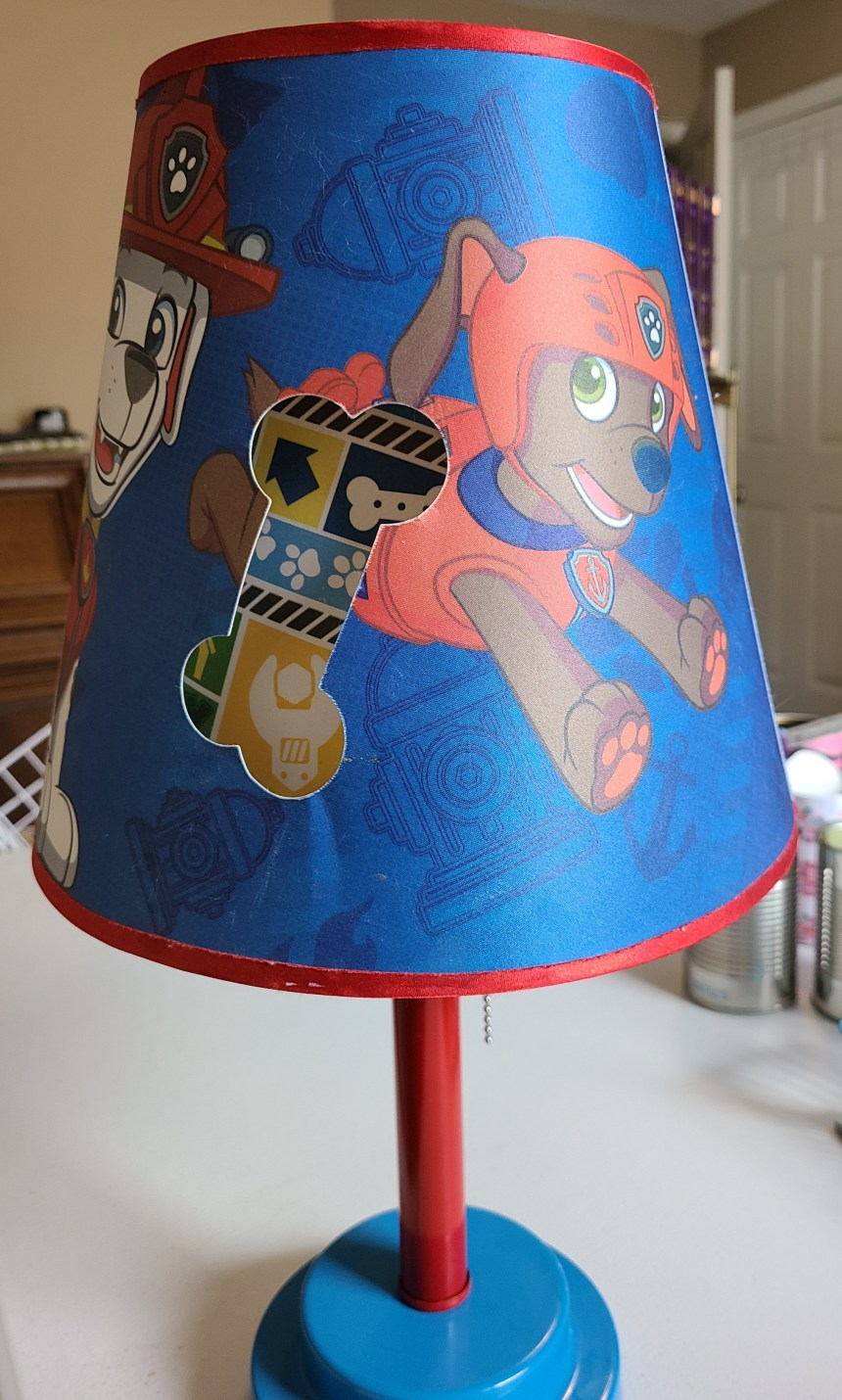 Paw Patrol lamp before it became the upcycled superhero lamp. Blue base, red pole the lightbulb screw into, lamp shade covered with Paw Patrol characters.