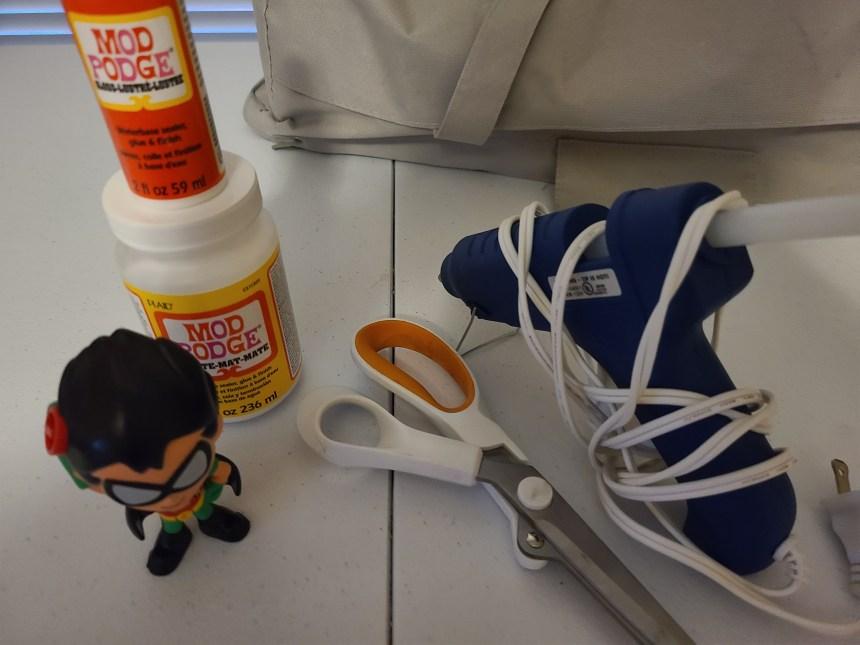 Supplies for the upcycled superhero lamp: scissors, hot glue gun & glue, Mod Podge, superhero figurine.