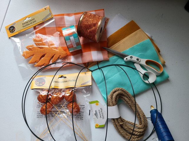 Supplies needed for Dollar Tree pumpkin wreath: pumpkin wreath form, glitter styrofoam pumpkins, 2 ribbons, orange and white buffalo check fabric, & nautical rope.