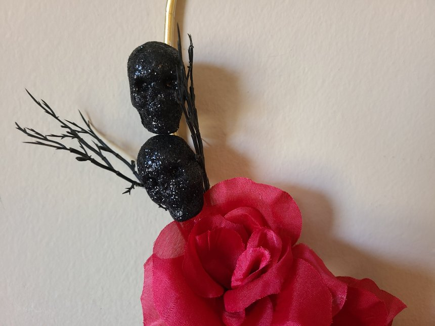 Edge of Halloween hoop wreath with black glitter skulls and branches glued on with scarlet/burgundy roses below them.