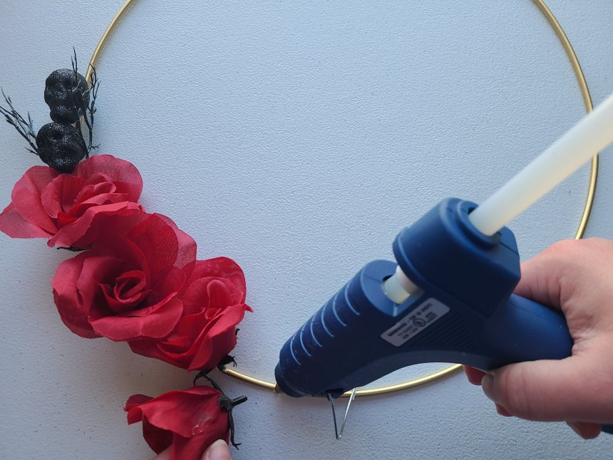 Adding glue to the gold Halloween hoop wreath while holding another rose to put on top of the glue.