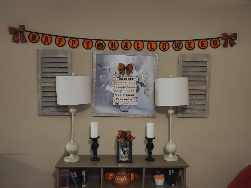 Completed Halloween Dollar Tree sign hung on a larger regular piece of home decor with Happy Halloween banner hung above.