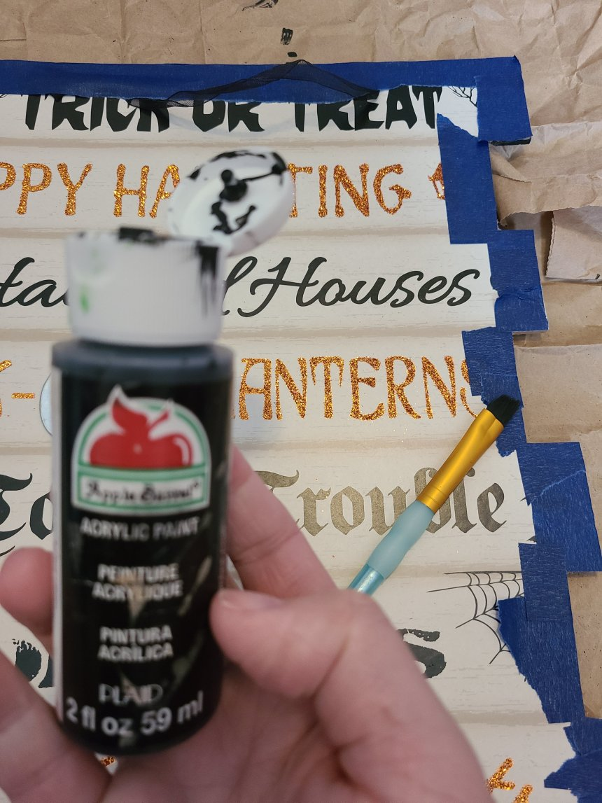 Black acrylic paint in front of the Halloween Dollar Tree sign,