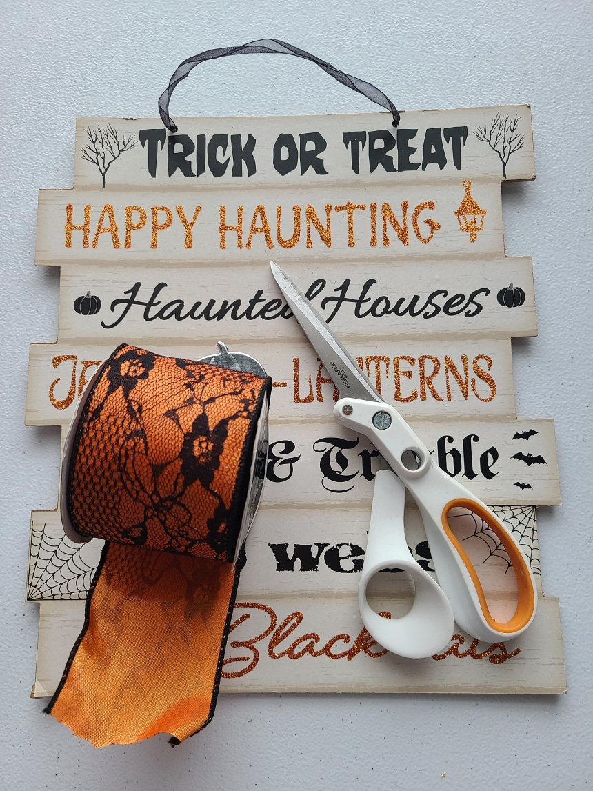 Supplies needed for the Halloween Dollar  Tree sign upcycle: sign, scissors, orange and black lace ribbon.