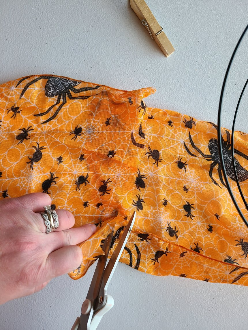 Cutting the excess scarf from to part that will be clothes-pinned to the Halloween pumpkin wreath.