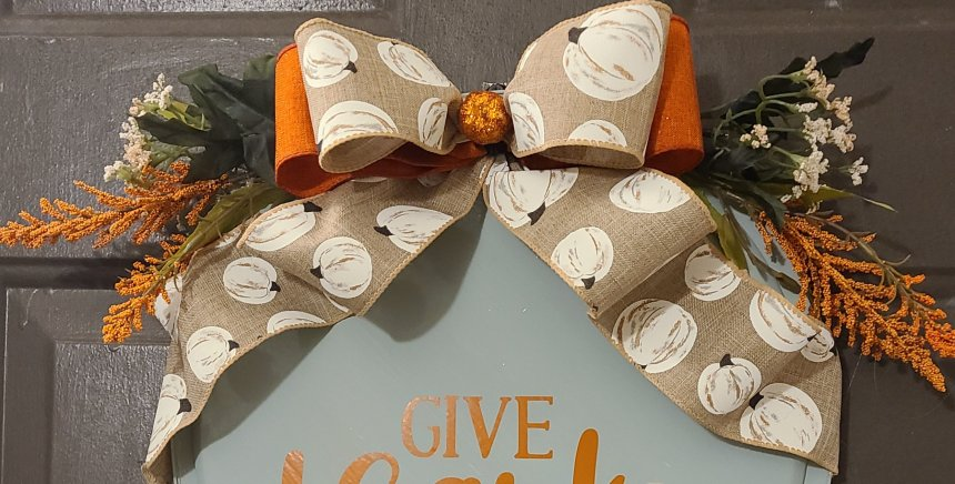 """Top of fall pizza pan wreath: sage with orange bow and beige bow with white pumpkins with black stems on it. Greenery juts out from behind the bows, in green, white, and orange. The middle of the bow is covered by a small glitter styrofoam pumpkin. The top of the saying """"give"""" from the entire phrase """"give thanks"""" can be seen."""