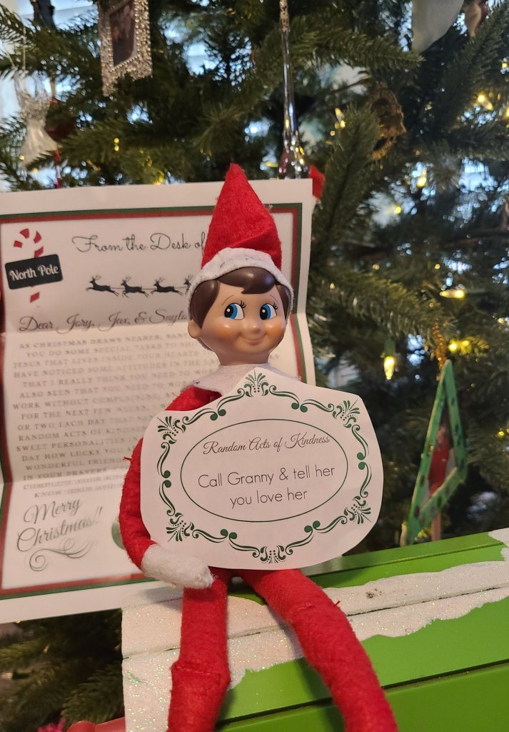 Elf holding RAOK and letter from Santa