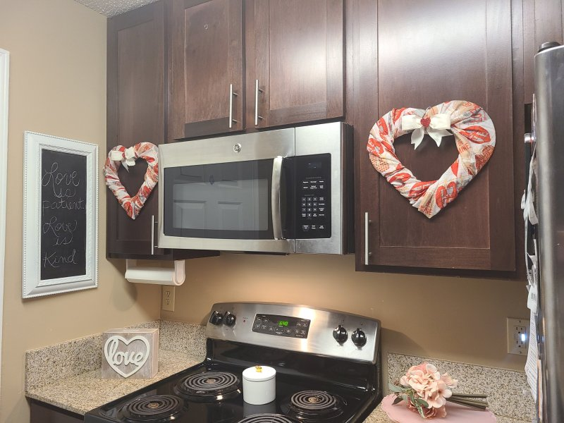 DIY Valentine's wreaths hung on two kitchen cabinet doors.