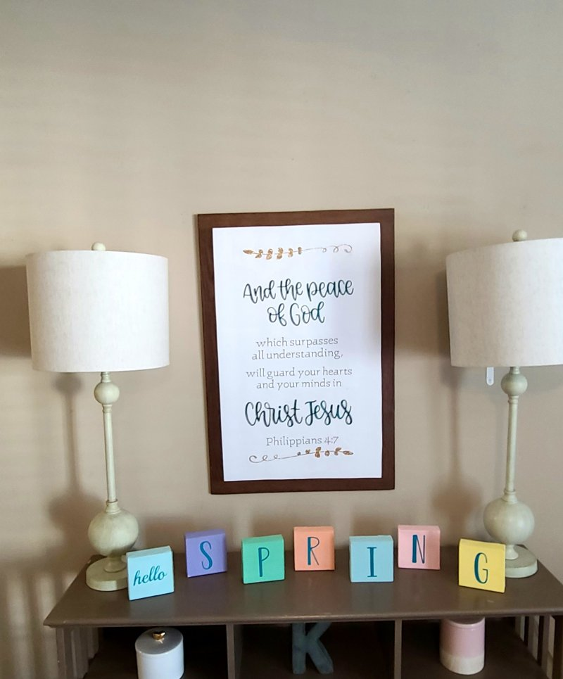 "Large farmhouse sign hanging above an entry-way table over blocks saying ""hello"" then spring spelled out with individual blocks."