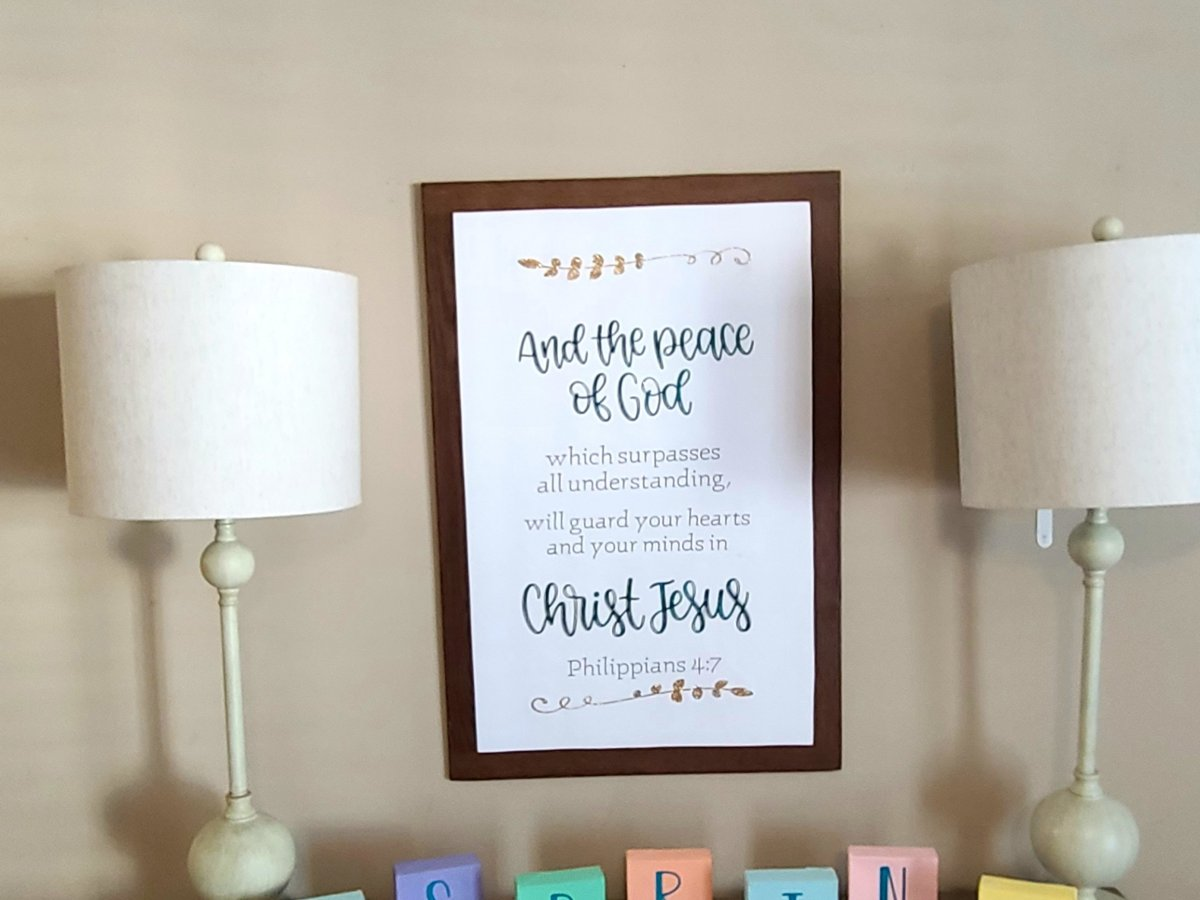 """Large farmhouse sign hanging above an entry-way table over blocks saying """"hello"""" then spring spelled out with individual blocks."""