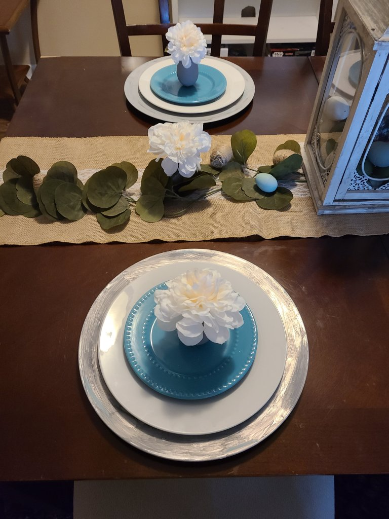 Easter tablescape with burlap and lace table runner and two place settings with gray charger, white plate, and robin's egg blue dessert plate. On top of the plate is an egg vase with white flower in it.