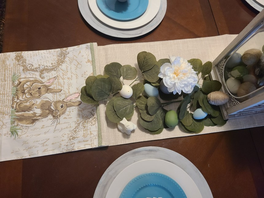 Easter tablescape with rabbit table runner with greenery, chalk painted eggs, and egg vases with white flower.