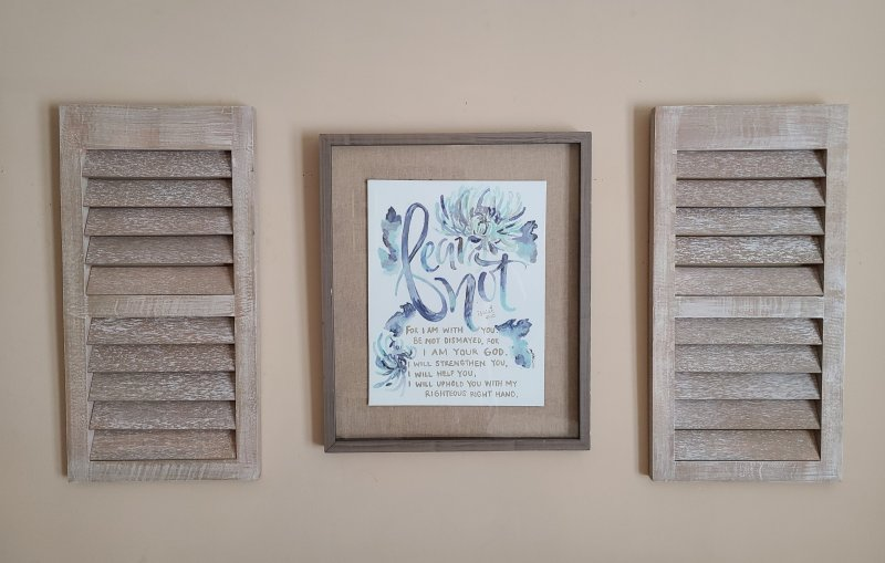 Hung wall art refab centered by two shutters.