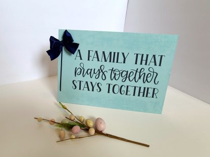 Robin's egg blue sign with gray vinyl quote. Navy blue leather cord along the side with a navy bow.