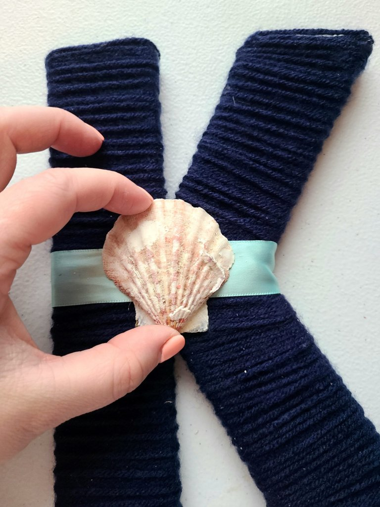 shell added on to of the ribbon on the nautical initial.