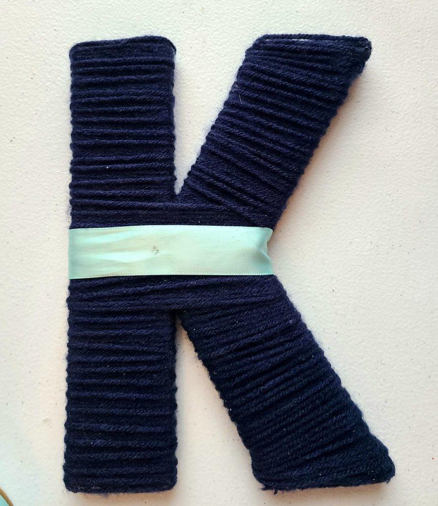 Satin ribbon wrapped around the K.