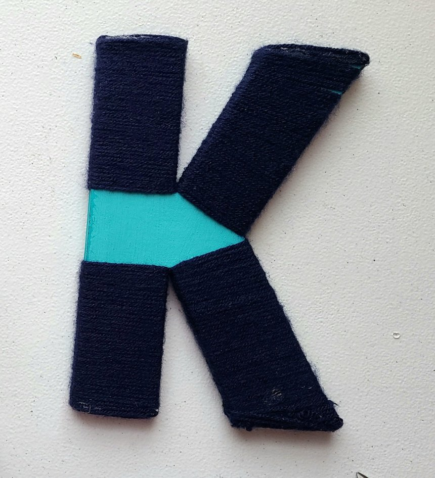 All four branches of the nautical initial K wrapped with navy yarn.