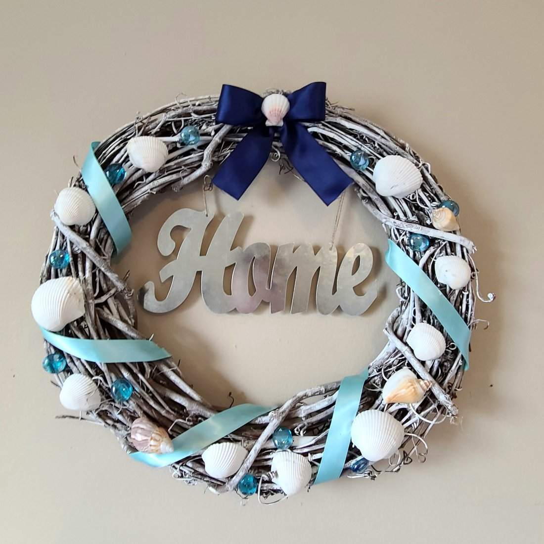 """Beach wreath, grapevine form, robin's egg blue satin ribbon wound around, navy satin ribbon at the top with a small seashell in the middle of the bow. Galvanized silver word """"home"""" in the middle of the wreath."""